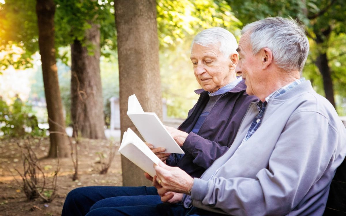 Two senior men reading books in park. One is reading a passage to his amused partner.
